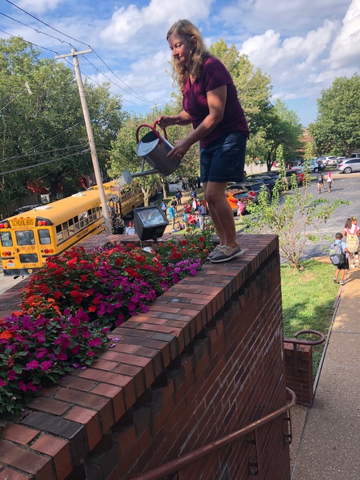 Debi watering Marine flowers at dismissal.